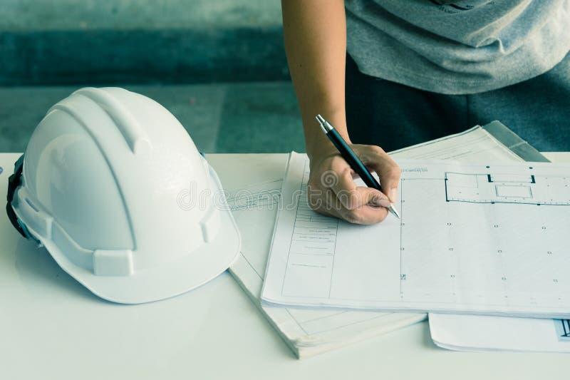 Sluit omhoog van ingenieurshanden die aan lijst werken, hij de schets van het tekeningsproject in bouwwerf of bureau stock afbeeldingen