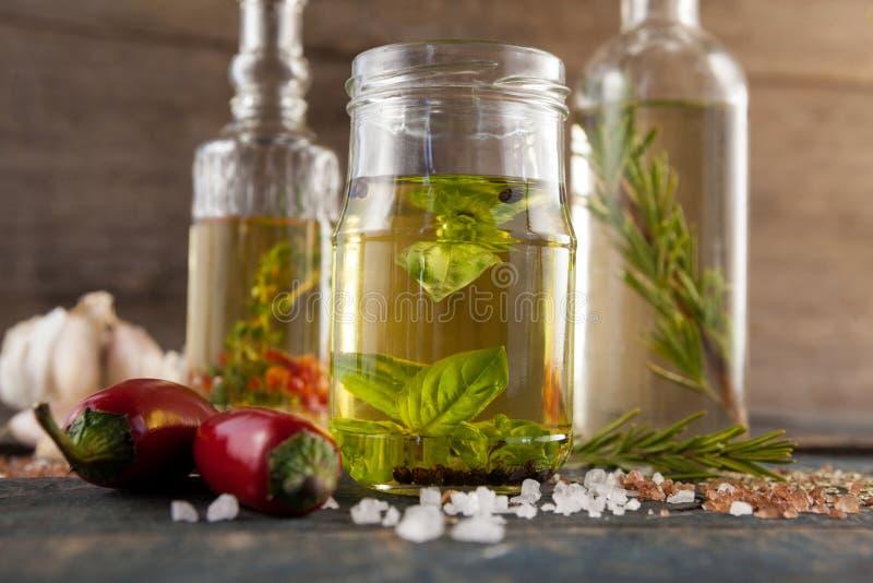 Sluit omhoog van Ingrediënten door kruid met olie in container stock afbeelding