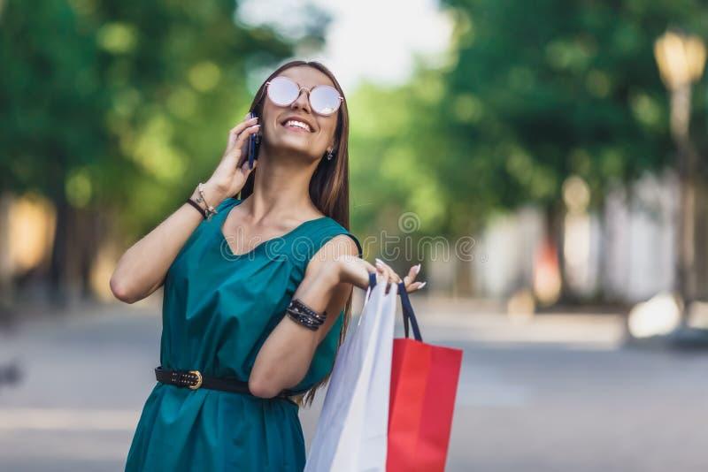 Sluit omhoog van jong charmant donker-haired Kaukasisch wijfje met het winkelen zakken die met tanden glimlachen en op telefoon s stock afbeeldingen