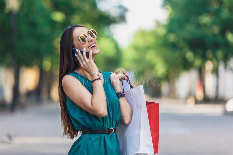 Sluit omhoog van jong charmant donker-haired Kaukasisch wijfje met het winkelen zakken die met tanden glimlachen en op telefoon s royalty-vrije stock foto's