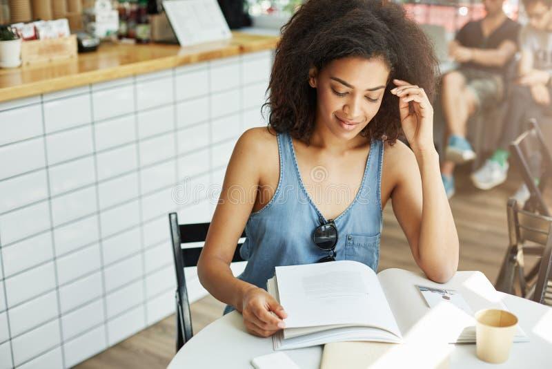 Sluit omhoog van jong mooi charmant donker-gevild studentenmeisje met krullend haar in modieuze uitrustingszitting in koffie daar stock foto's