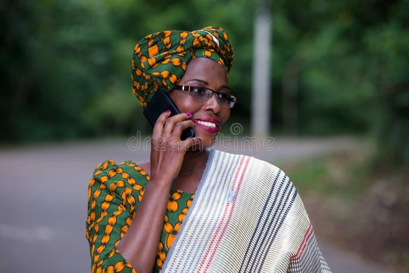 Sluit omhoog van jonge Afrikaanse vrouw met mobiele telefoon, gelukkig royalty-vrije stock foto