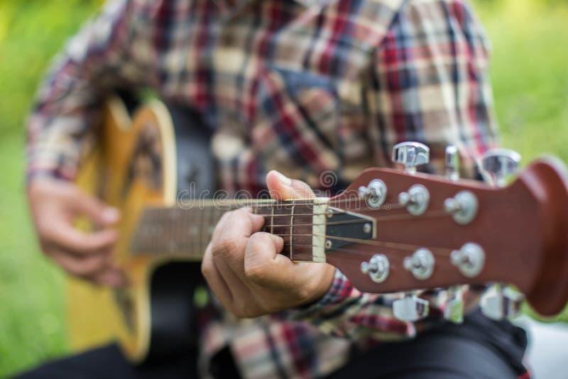 Sluit omhoog van jonge hipstermens uitgeoefende gitaar in het park, gelukkig en geniet van speel gitaarreeks stock foto