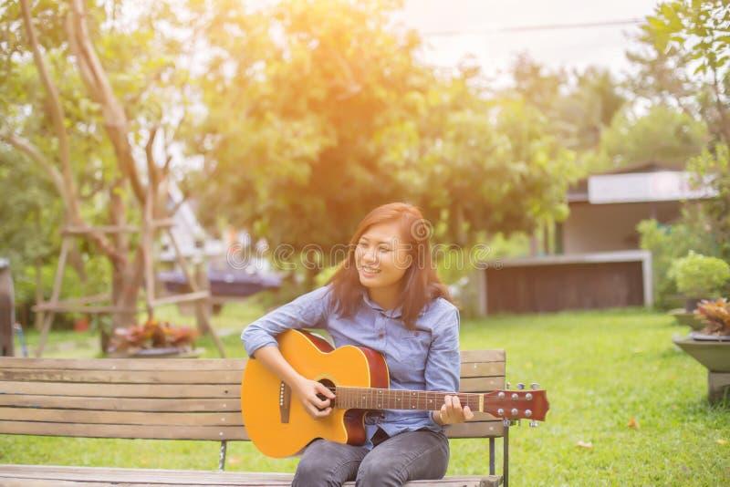 Sluit omhoog van jonge hipstervrouw uitgeoefende gitaar in het park, gelukkig en geniet van speel gitaar stock foto