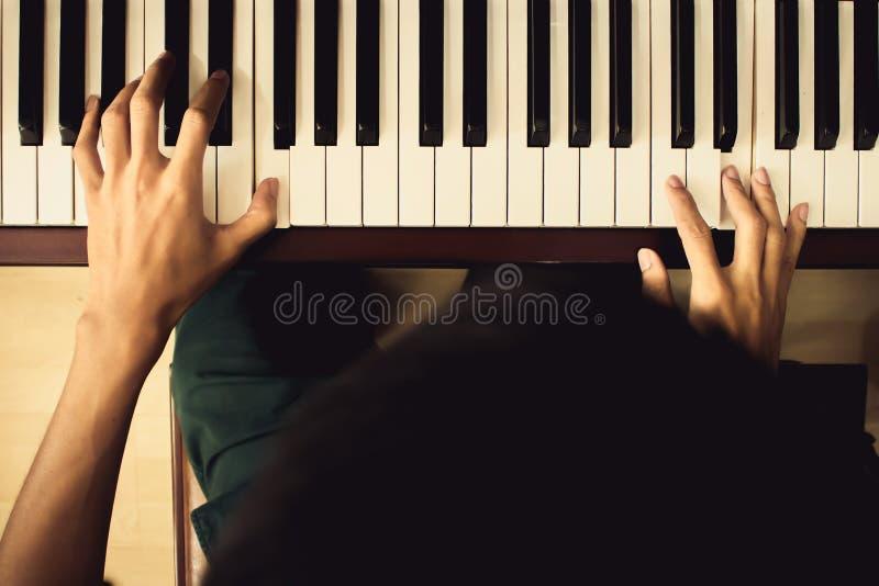 Sluit omhoog van jonge jongenshanden, spelend piano uitstekende toonfilter stock afbeelding
