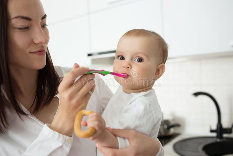 Sluit omhoog van jonge knappe moeder die haar houden weinig zoon op handen en hem voeden, met lepel Kind die babyvoedsel eten stock fotografie