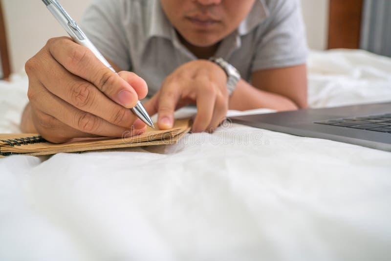Sluit omhoog van jonge mens het schrijven nota's stock fotografie