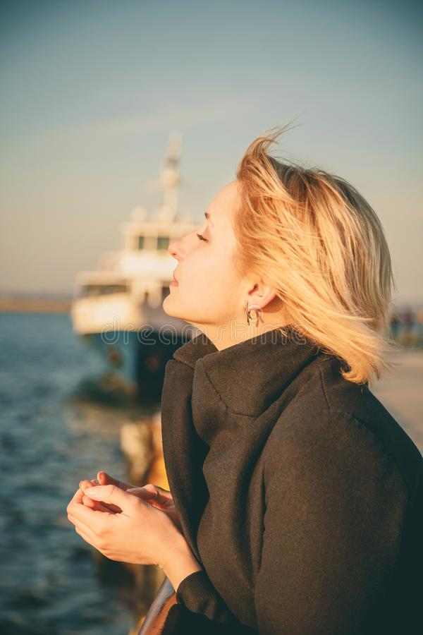 Sluit omhoog van jonge mooie vrouw, meisje die bij pijler bij zonsondergang met gesloten ogen van vrijheid, gelukkig openluchtpor stock afbeeldingen