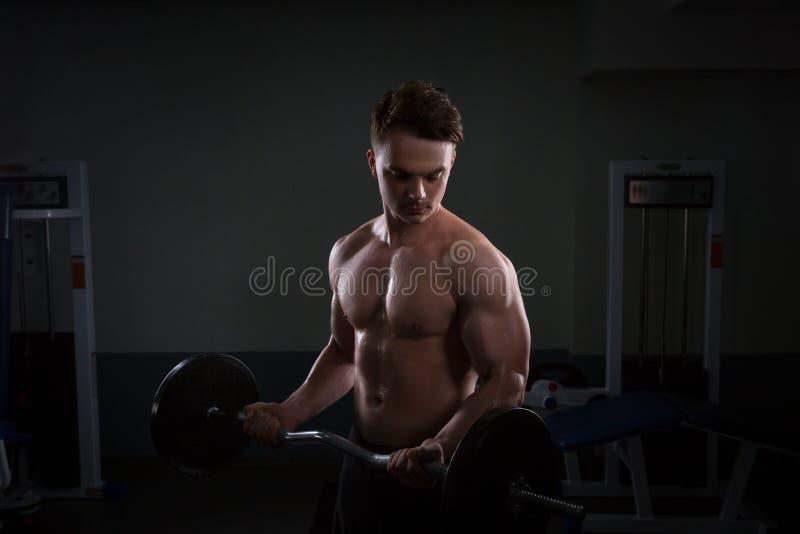 Sluit omhoog van jonge spiermens het opheffen gewichten over donkere achtergrond stock afbeelding