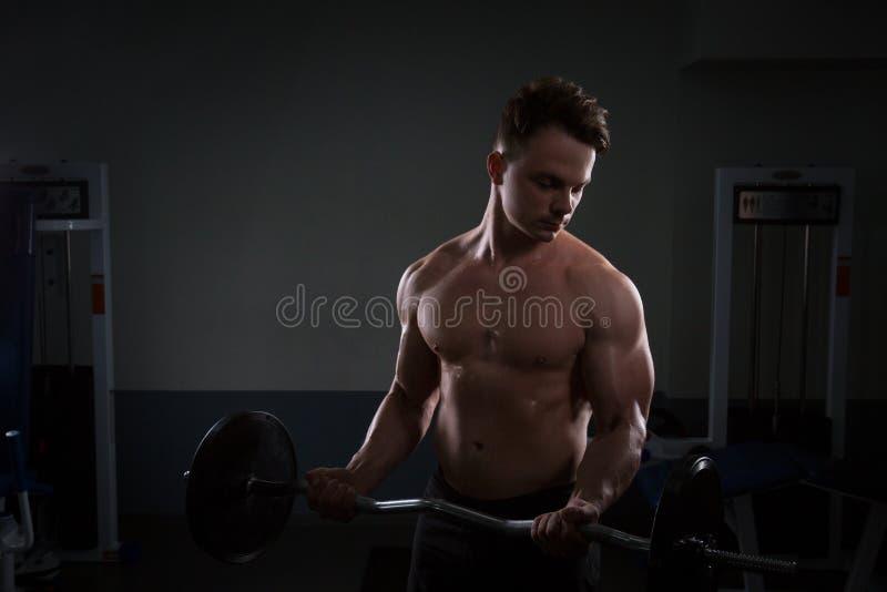 Sluit omhoog van jonge spiermens het opheffen gewichten over donkere achtergrond royalty-vrije stock foto