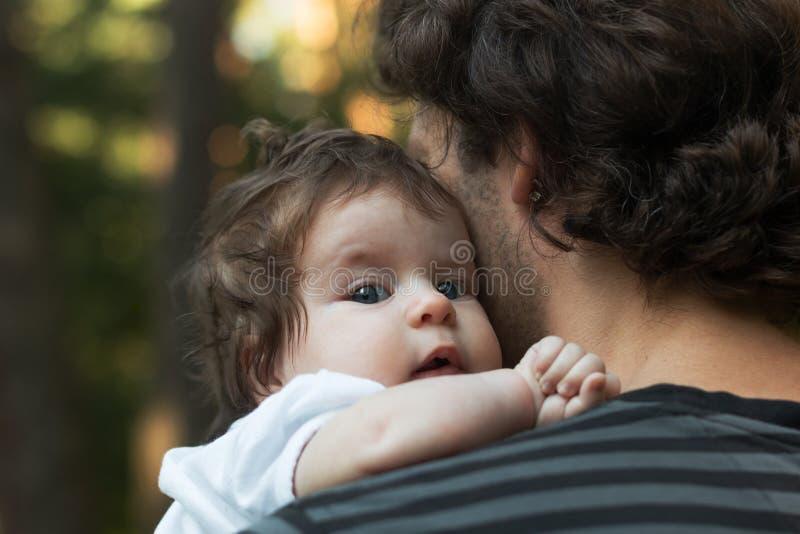 Sluit omhoog van jonge vader die zijn pasgeboren baby houden Nadruk op de baby` s blauwe ogen royalty-vrije stock fotografie