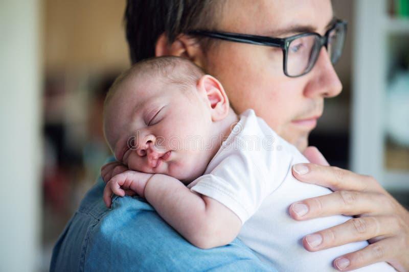 Sluit omhoog van jonge vader die zijn pasgeboren babyzoon houden royalty-vrije stock afbeeldingen