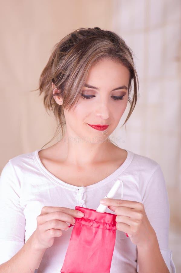 Sluit omhoog van jonge vrouw die een menstruatie katoenen tampon binnen van een rode zak introduceren in een vage achtergrond royalty-vrije stock fotografie