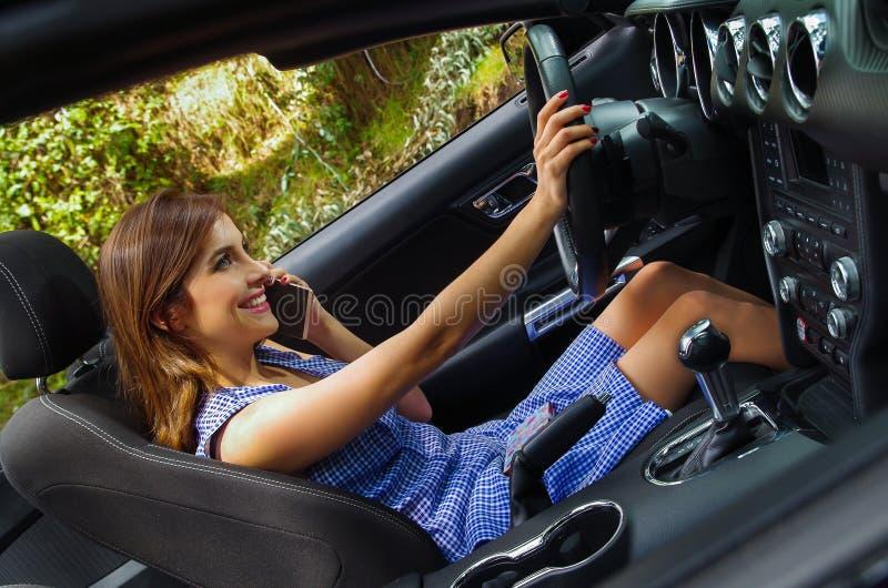 Sluit omhoog van jonge vrouw gebruikend haar cellphone binnen van de zwarte auto, terwijl het drijven van haar auto met één hand, royalty-vrije stock afbeeldingen