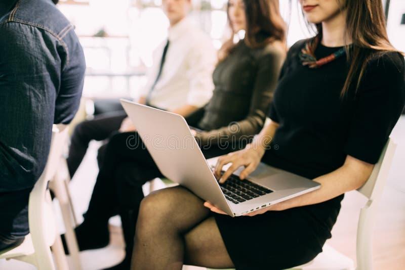Sluit omhoog van jonge vrouw met laptop op vergadering van het teambuilding van het werk of presentatie in bureau stock afbeeldingen