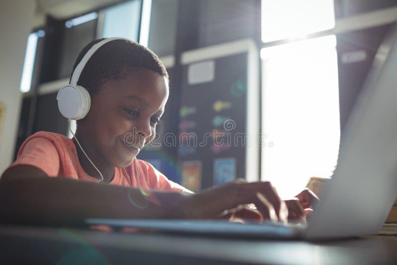 Sluit omhoog van jongen het luisteren muziek terwijl het gebruiken van laptop stock fotografie