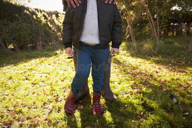 Sluit omhoog van Jongen met Vader Standing In Autumn Garden royalty-vrije stock foto