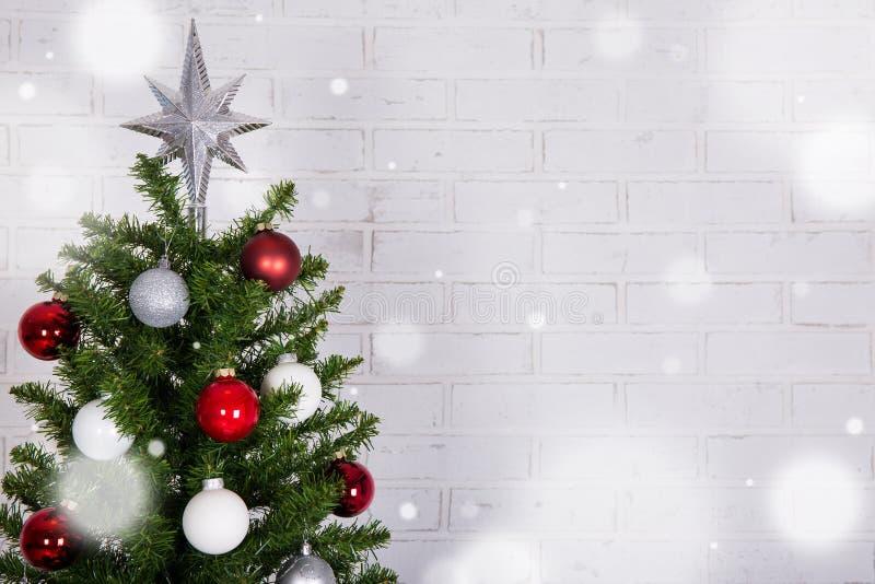 Sluit omhoog van Kerstmisboom over witte bakstenen muur met sneeuw stock foto's