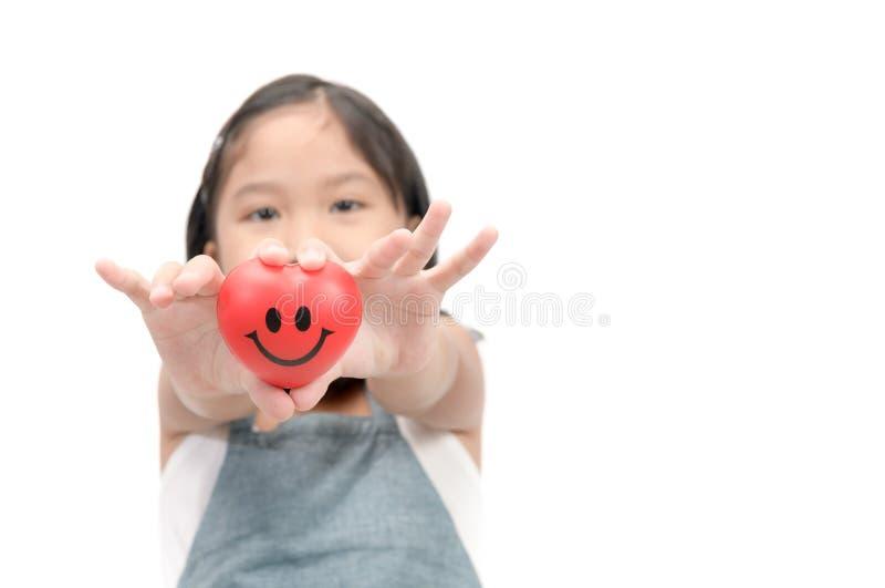 Sluit omhoog van kindhanden die glimlach rood hart geven stock foto's