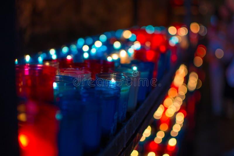 Sluit omhoog van kleurrijke kaarsen in een donkere geestelijke scène Herdenking, begrafenis, herdenkings Godsdienstige Symboliek stock fotografie