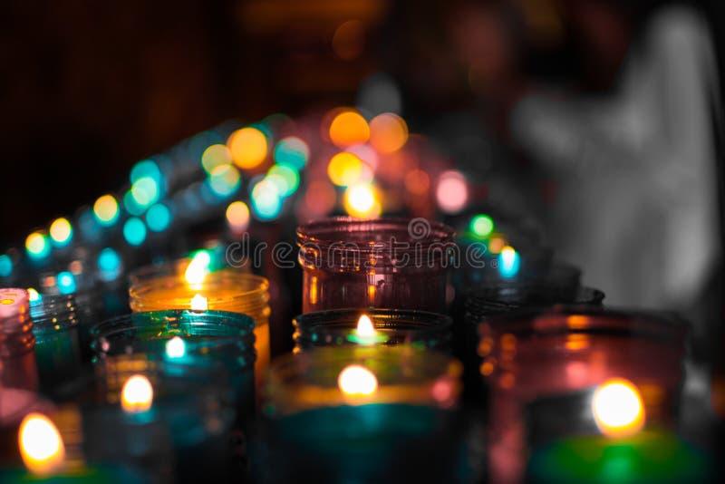 Sluit omhoog van kleurrijke kaarsen in een donkere geestelijke scène Herdenking, begrafenis, herdenkings Godsdienstige Symboliek royalty-vrije stock afbeeldingen
