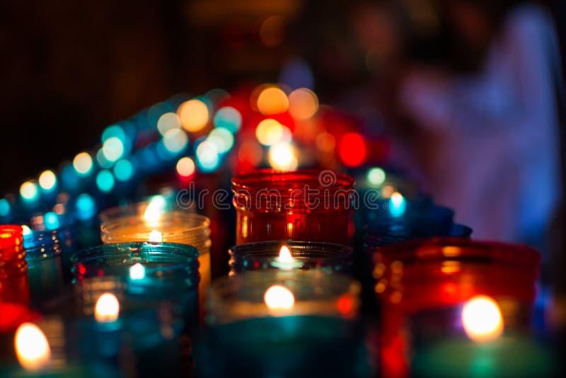 Sluit omhoog van kleurrijke kaarsen in een donkere geestelijke scène Herdenking, begrafenis, herdenkings Godsdienstige Symboliek royalty-vrije stock fotografie