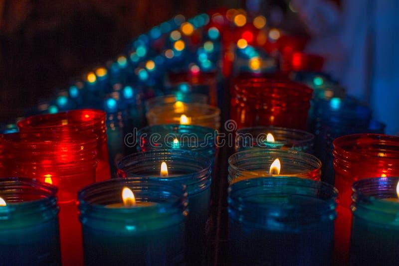 Sluit omhoog van kleurrijke kaarsen in een donkere geestelijke scène Herdenking, begrafenis, herdenkings Godsdienstige Symboliek stock foto's