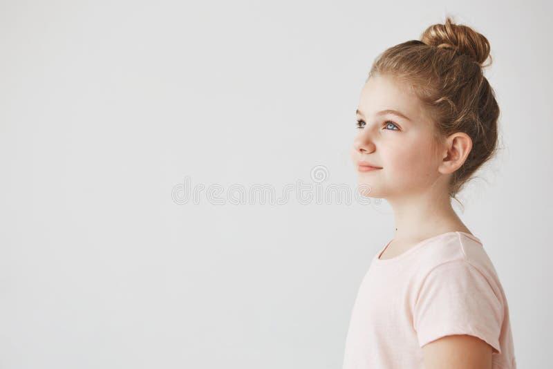 Sluit omhoog van knap meisje met blondehaar in broodjeskapsel, die zich in drie bevinden - kwarten, opzij kijkend met stock afbeeldingen