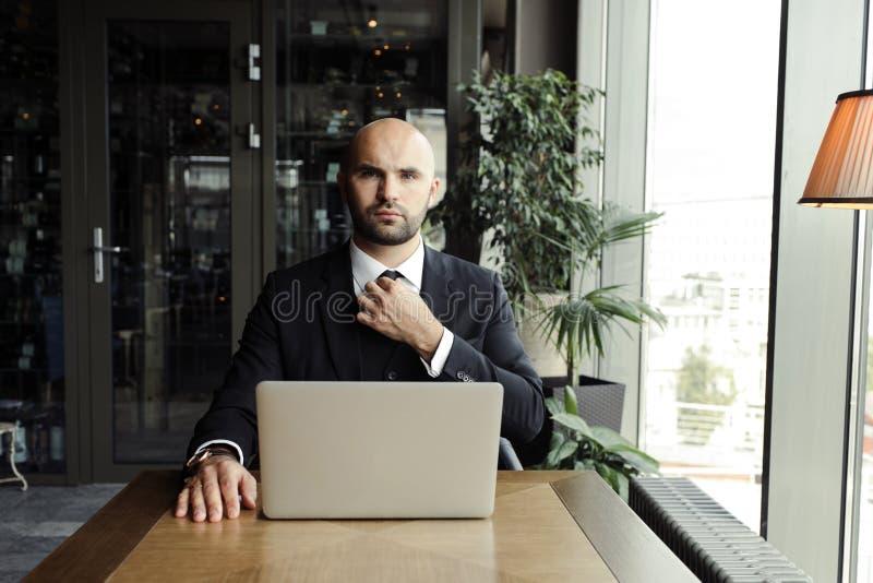 Sluit omhoog van knappe zakenman, die aan laptop in restaurant werken royalty-vrije stock foto's