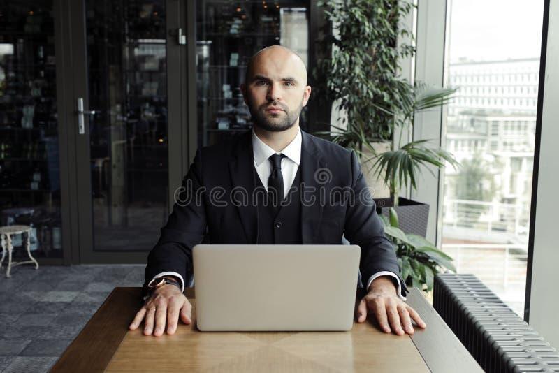 Sluit omhoog van knappe zakenman, die aan laptop in restaurant werken royalty-vrije stock foto