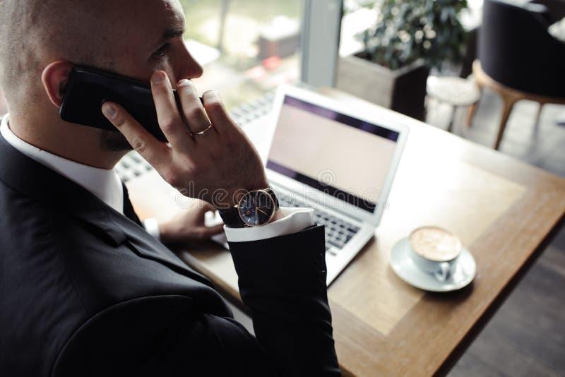 Sluit omhoog van knappe zakenman, die aan laptop in restaurant werken royalty-vrije stock afbeelding