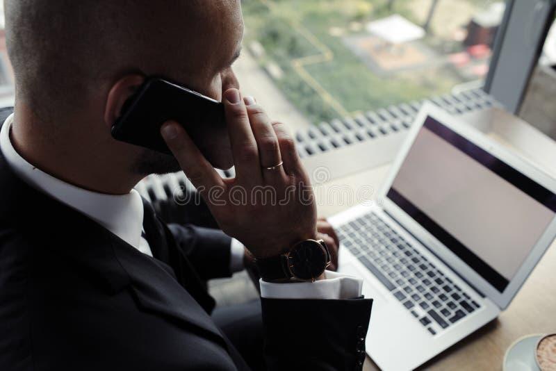Sluit omhoog van knappe zakenman, die aan laptop in restaurant werken stock foto's