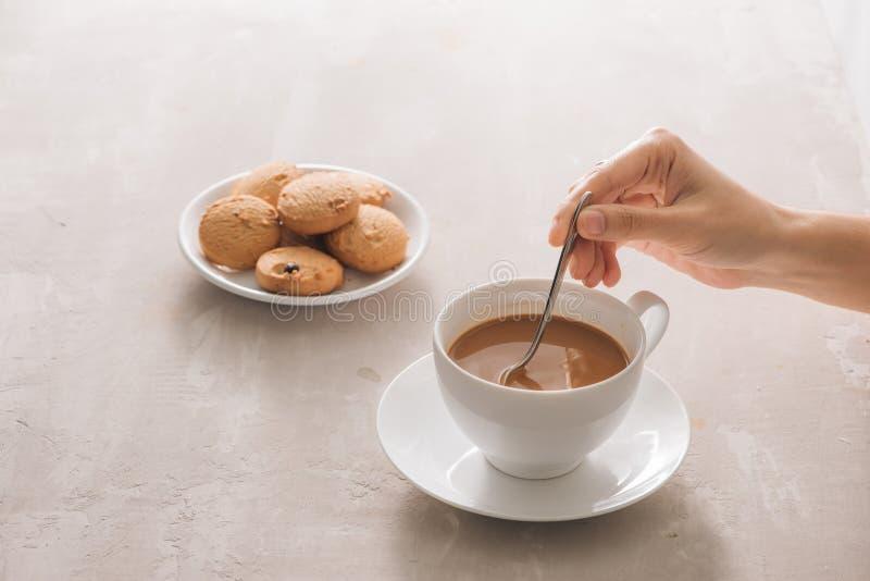Sluit omhoog van koekje en hand het bewegen kop thee/koffie stock foto's