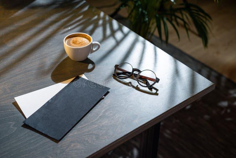 Sluit omhoog van koffiekop, lege enveloppen en glazen op donkere houten lijst stock foto's