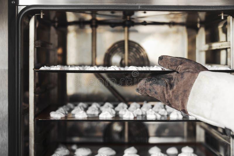 Sluit omhoog van kok die schuimgebakjekoekjes in de oven zetten royalty-vrije stock foto's