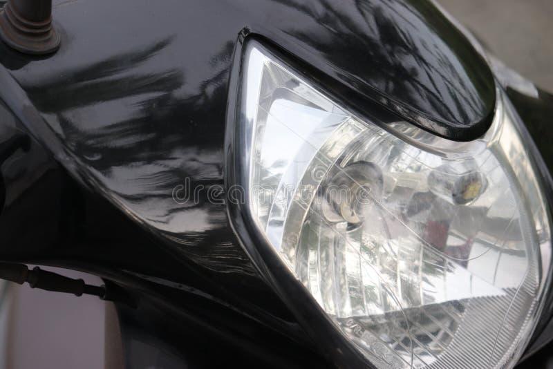 Sluit omhoog van koplamp van een zwarte autoped stock fotografie