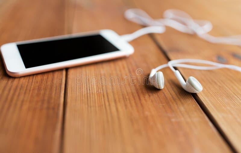 Sluit omhoog van lege smartphone en oortelefoons op hout stock foto