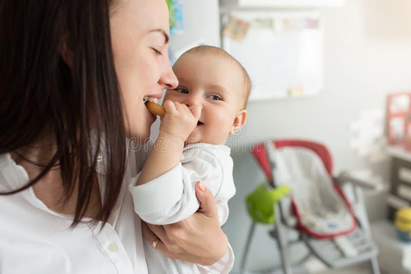 Sluit omhoog van leuke pasgeboren gelukkige moeder met koekje voeden, en babyjongen die opzij glimlachen kijken Levensstijl, fami stock afbeelding