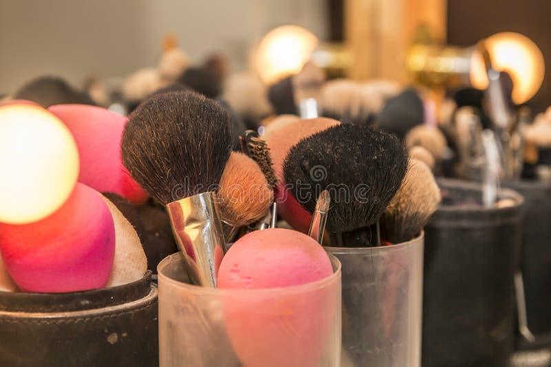 Sluit omhoog van make-upborstels naast een spiegel met schijnwerpers royalty-vrije stock afbeeldingen