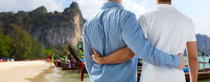 Sluit omhoog van mannelijk vrolijk paar die op strand koesteren royalty-vrije stock foto