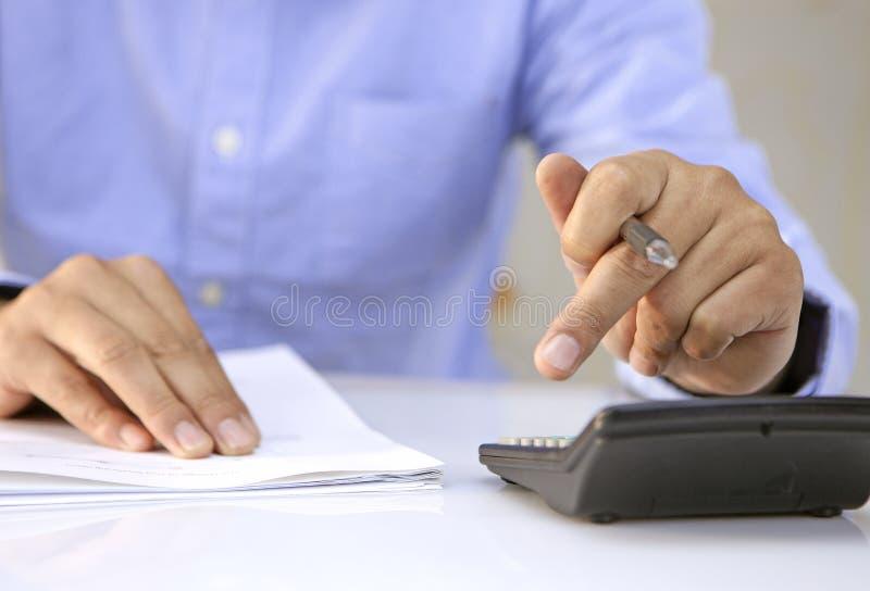 Sluit omhoog van mannelijke accountant of bankier die berekeningen maken stock foto's