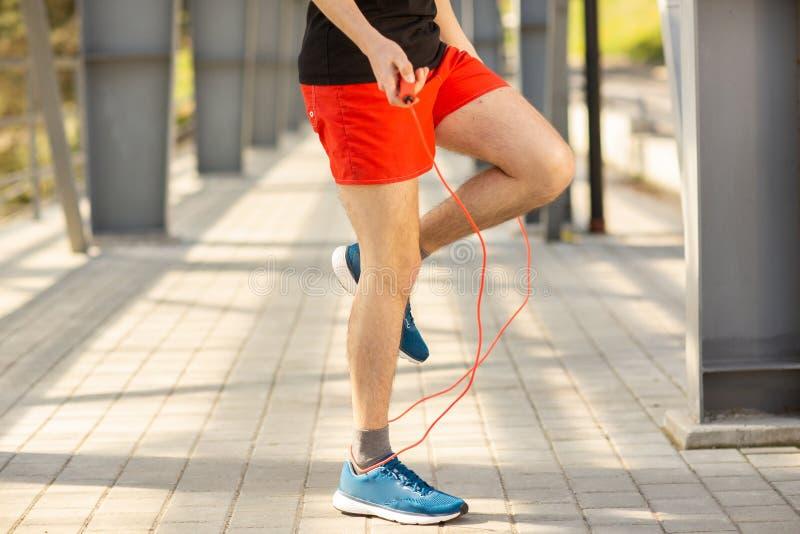 Sluit omhoog van mannelijke benen die met springtouw in openlucht overslaan Het uitoefenen en levensstijlconcept stock foto
