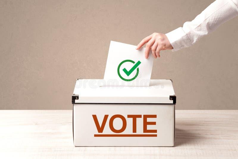 Sluit omhoog van mannelijke hand zettend stem in een stembus stock afbeelding