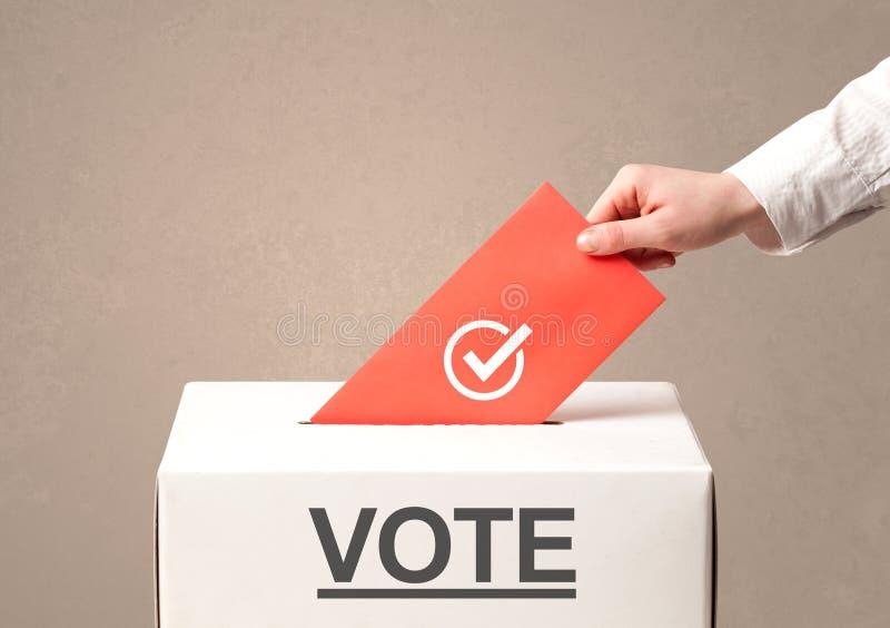 Sluit omhoog van mannelijke hand zettend stem in een stembus stock fotografie