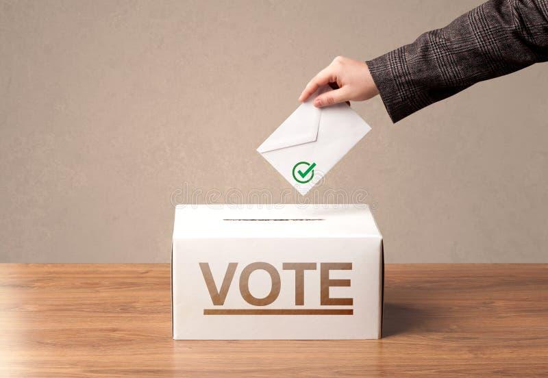 Sluit omhoog van mannelijke hand zettend stem in een stembus stock foto
