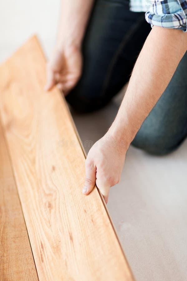 Sluit omhoog van mannelijke handen die houten bevloering intalling royalty-vrije stock foto