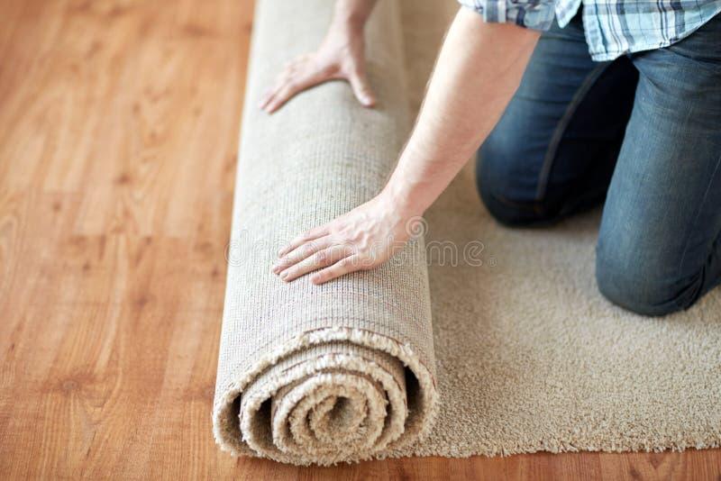 Sluit omhoog van mannelijke handen die tapijt rollen stock afbeeldingen