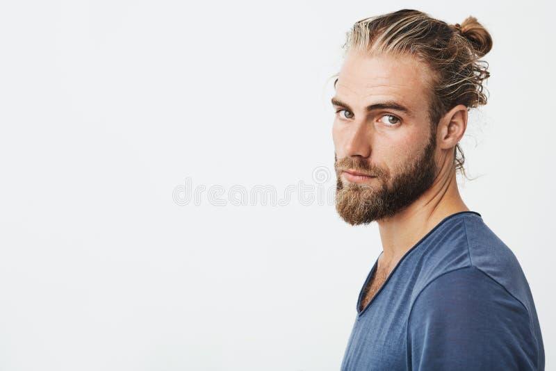 Sluit omhoog van mannelijke knappe kerel met modieus kapsel en baard kijkend in camera, houdend hoofd in drie - kwarten stock fotografie