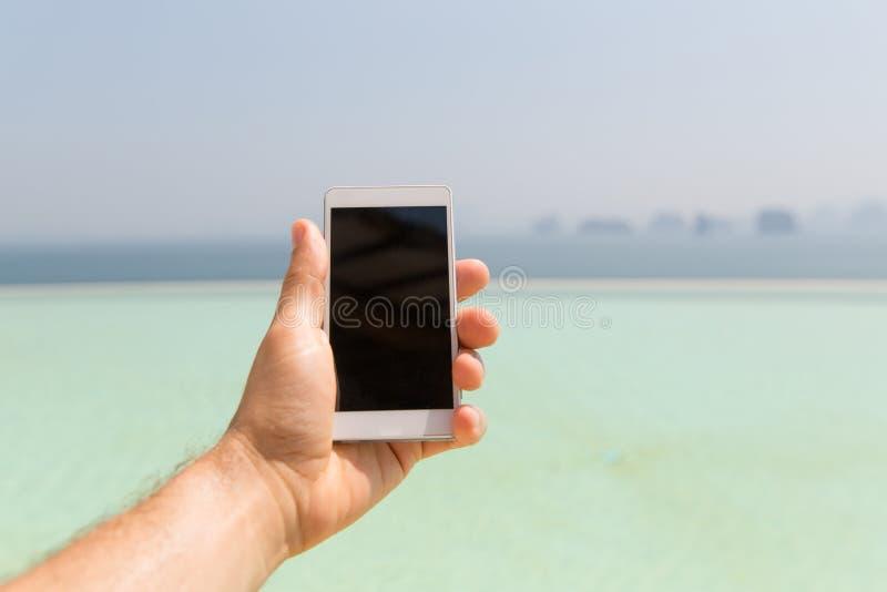 Sluit omhoog van mannelijke smartphone van de handholding op strand royalty-vrije stock afbeelding