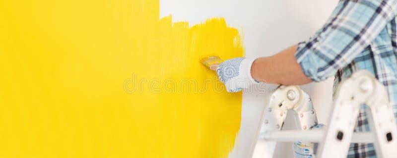 Sluit omhoog van mannetje die in handschoenen een muur schilderen stock afbeeldingen